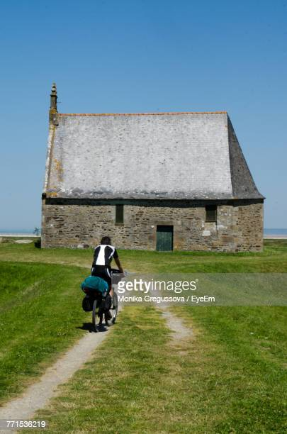 rear view of mature man riding bicycle towards chapel - monika gregussova stock pictures, royalty-free photos & images