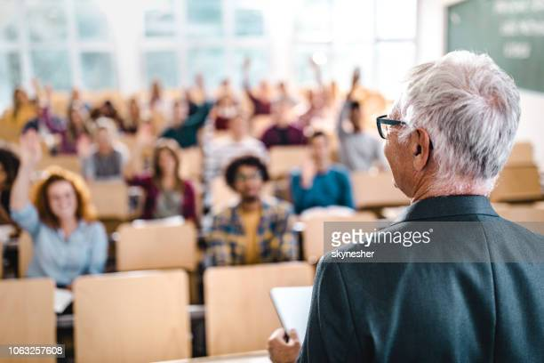 rear view of mature teacher giving a lecture in a classroom. - amphitheatre stock pictures, royalty-free photos & images
