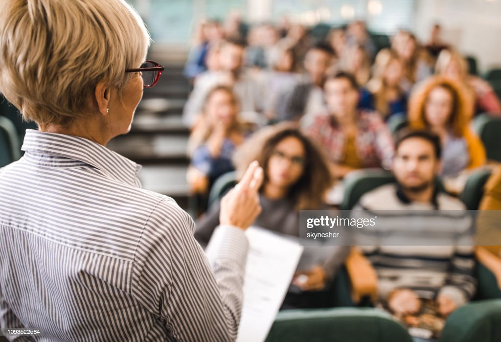 Rear view of mature teacher giving a lecture in a classroom. : Stock Photo