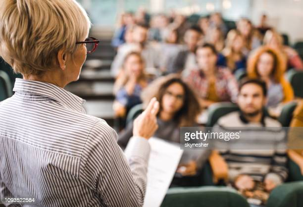 rear view of mature teacher giving a lecture in a classroom. - university stock pictures, royalty-free photos & images