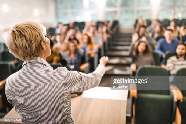 教室で講義をする成熟した教師の背面図。 - 円形劇場 ストックフォトと画像