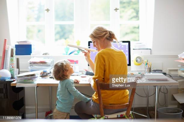 rear view of mature woman and boy sitting at computer playing with toy aeroplane - offspring stock pictures, royalty-free photos & images