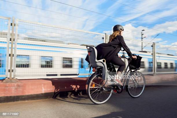 Rear view of mature woman cycling on road by fence against sky