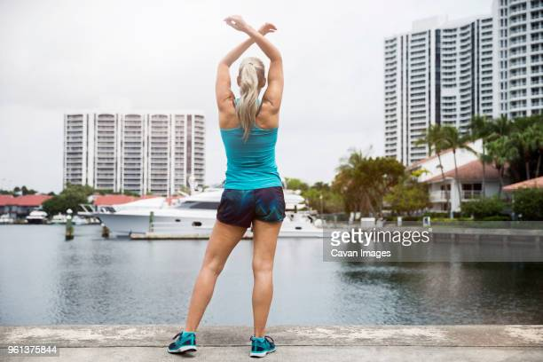 rear view of mature woman exercising on footpath by river - aventura stock pictures, royalty-free photos & images