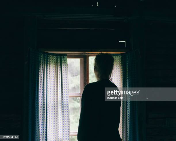 rear view of mature woman looking through window at home - 暗室 ストックフォトと画像