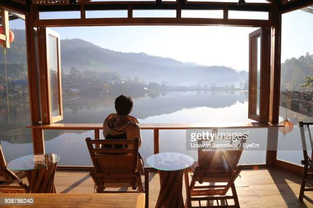 rear view of mature woman looking through window at home - admirer le paysage photos et images de collection