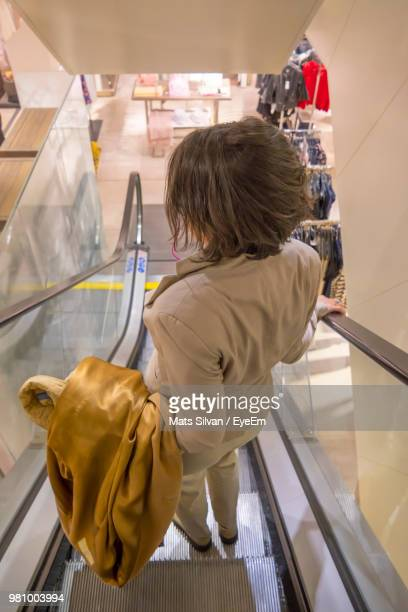 Rear View Of Mature Woman Moving Down On Escalator