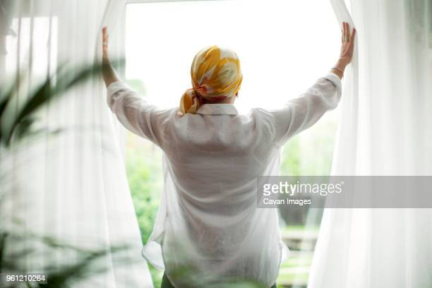 Rear view of mature woman opening curtains at window