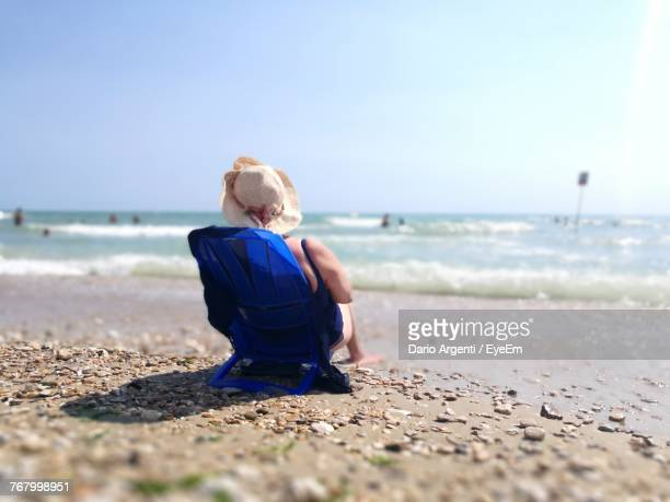 Rear View Of Mature Woman Relaxing On Deck Chair At Beach Against Clear Sky