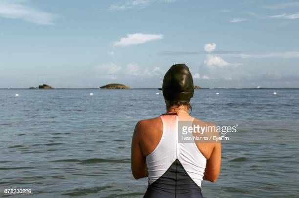 Rear View Of Mature Woman Standing In Sea Against Sky
