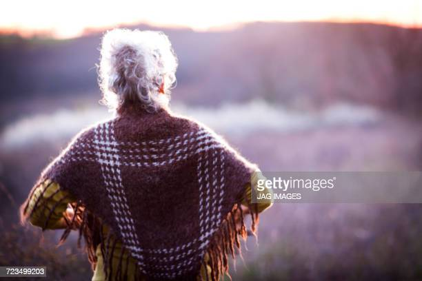 Rear view of mature woman watching sunset over rural landscape