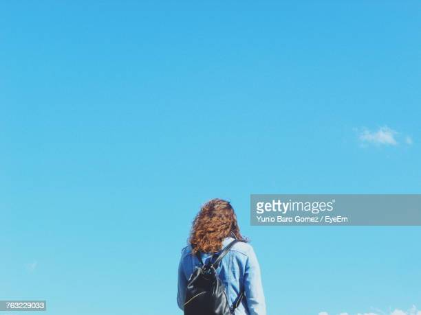 Rear View Of Mature Woman With Backpack Standing Against Blue Sky During Sunny Day