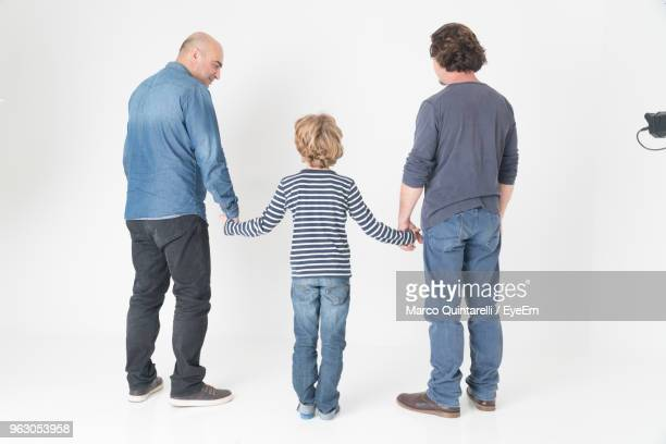 rear view of men and boy holding hands while standing against white background - dreiviertelansicht stock-fotos und bilder