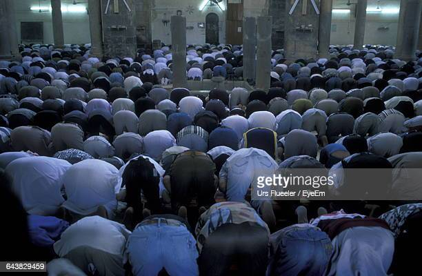 rear view of men bending over while praying in mosque - man bending over from behind stock photos and pictures