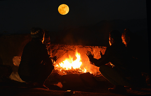 Rear View Of Men Crouching By Bonfire At Night - gettyimageskorea