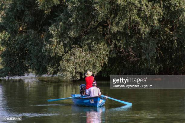 Rear View Of Men In Boat On Lake Against Trees