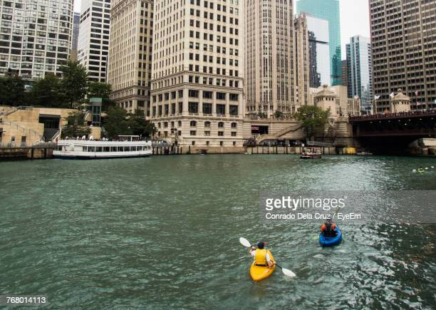 Rear View Of Men Kayaking In River By City