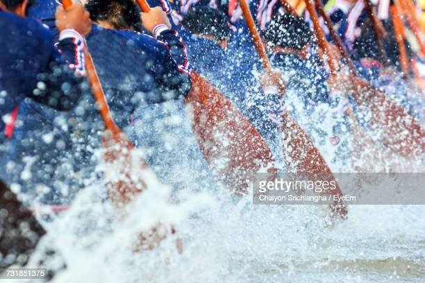 rear view of men oaring during boat race - sportmannschaft stock-fotos und bilder