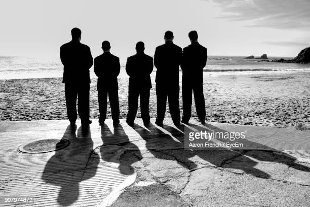 rear view of men standing against sea at beach - 5人 ストックフォトと画像