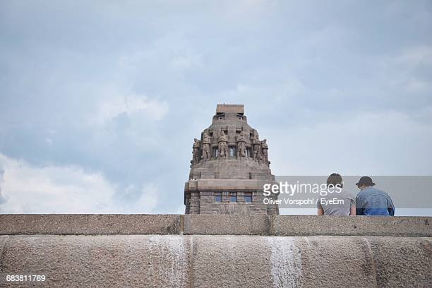 rear view of men standing at monument to the battle of the nations against sky - denkmal stock-fotos und bilder