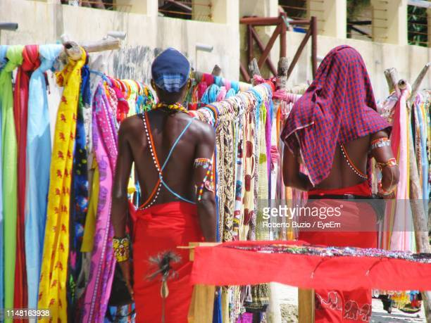 rear view of men standing in market - mombasa stock photos and pictures