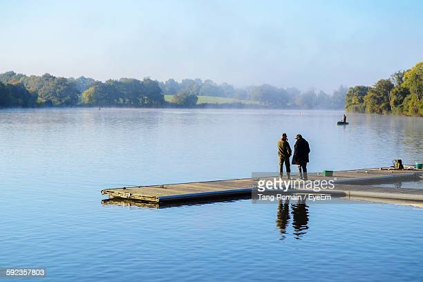 Rear View Of Men Standing On Pier Over Lake During Foggy Weather