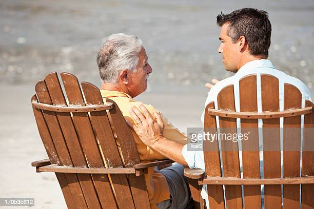 Rear view of men talking on beach