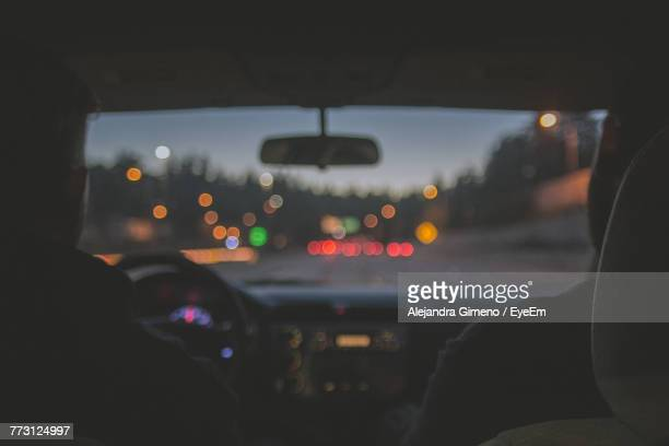 Rear View Of Men Traveling In Car At Night