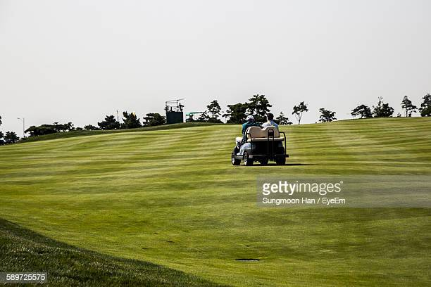 rear view of men traveling on golf cart against clear sky - songdo ibd stock pictures, royalty-free photos & images