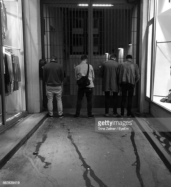 rear view of men urinating on gate by store - urinary system stock photos and pictures