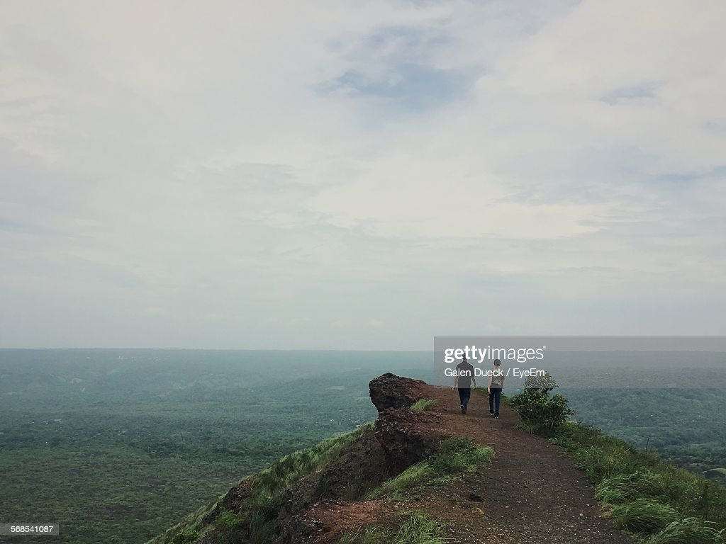 Rear View Of Men Walking On Cliff Against Cloudy Sky : Stock Photo