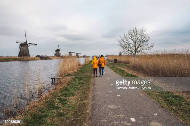 rear view of men walking on road against sky and windmills - bortes stock pictures, royalty-free photos & images