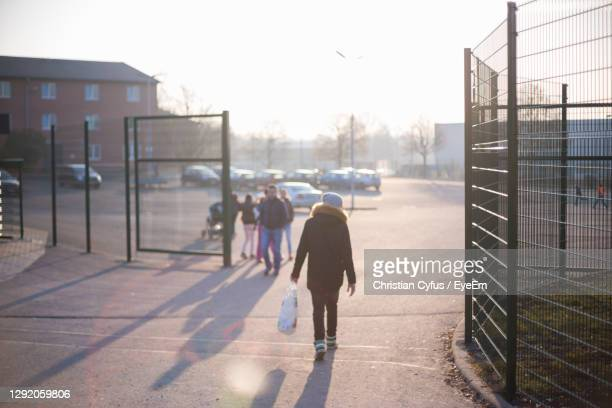rear view of men walking on sidewalk in city - refugee stock pictures, royalty-free photos & images
