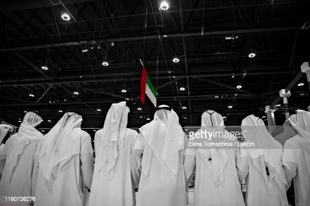 rear view of men wearing white traditional clothing with united arab emirates flag hanging from ceiling in background - traditional clothing stock pictures, royalty-free photos & images