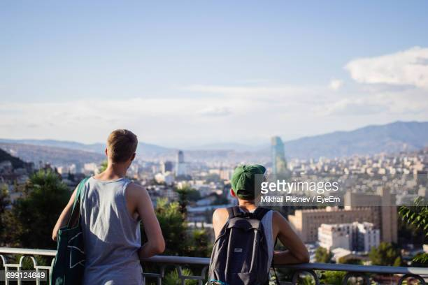 Rear View Of Men With Cityscape Against Sky