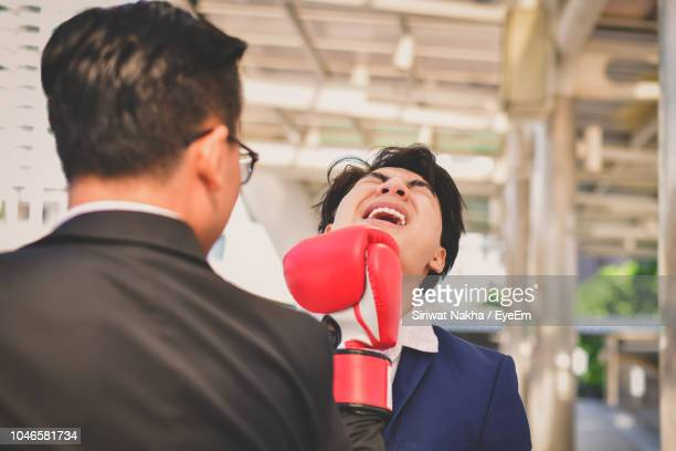 Rear View Of Mid Adult Businessman Punching Colleague