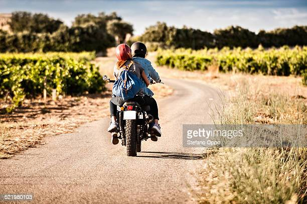 Rear view of mid adult couple riding motorcycle on winding rural road, Cagliari, Sardinia, Italy