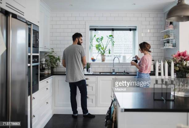 rear view of mid adult couple working in kitchen at home - dreiviertelansicht stock-fotos und bilder