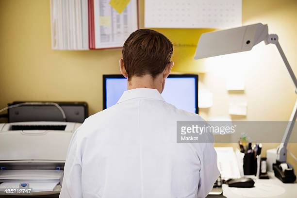 Rear view of mid adult male doctor using computer in clinic