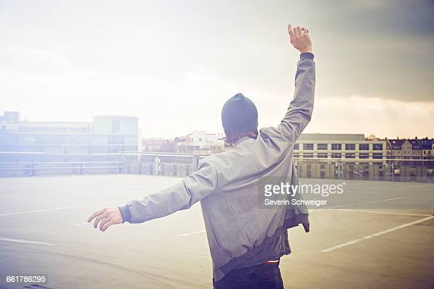 Rear view of mid adult man dancing on rooftop parking lot