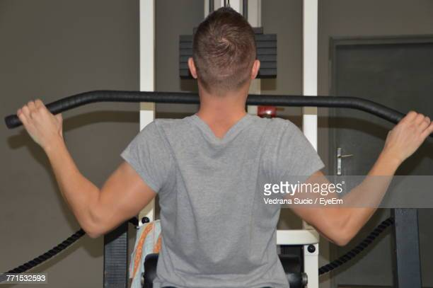 Rear View Of Mid Adult Man Exercising In Gym