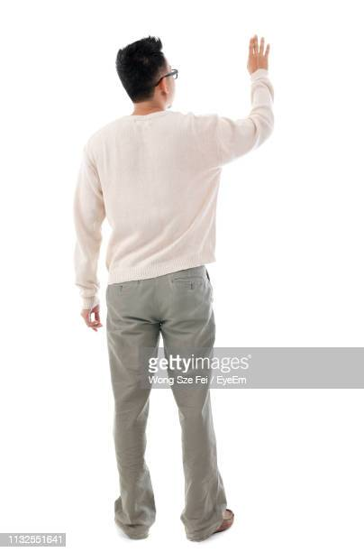 rear view of mid adult man gesturing while standing against white background - op de rug gezien stockfoto's en -beelden