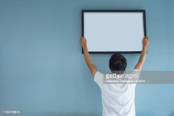 rear view of mid adult man hanging blank picture frame on wall at home - hanging stock pictures, royalty-free photos & images