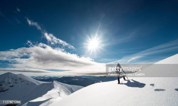 rear view of mid adult man hiking on snowcapped mountain against cloudy sky - fabrizio zampetti foto e immagini stock