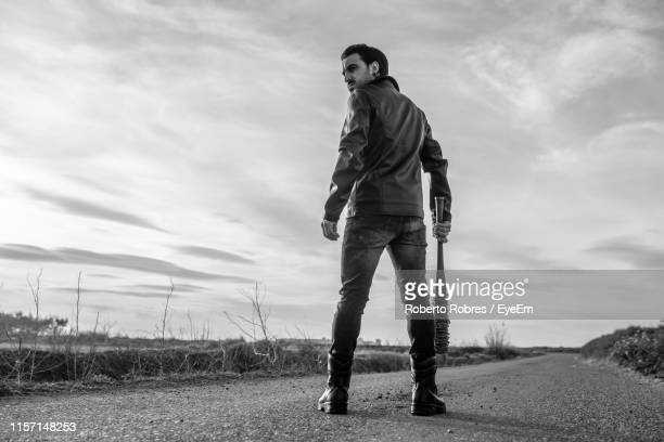 rear view of mid adult man holding barbed wire wrapped baseball bat while standing on road against sky - baseball bat stock pictures, royalty-free photos & images