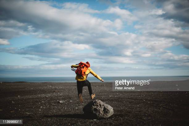 rear view of mid adult man jumping over boulder on volcanic landscape, iceland - boulder rock stock pictures, royalty-free photos & images