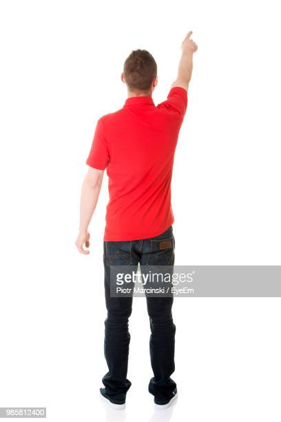 rear view of mid adult man pointing against white background - op de rug gezien stockfoto's en -beelden