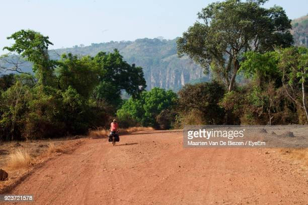 Rear View Of Mid Adult Man Riding Motorcycle On Dirt Road Against Trees