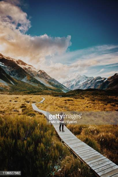 rear view of mid adult man standing on boardwalk against sky - wellington new zealand stock pictures, royalty-free photos & images