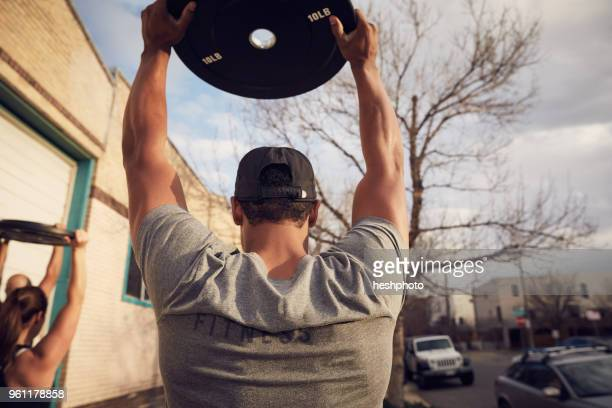rear view of mid adult man with arms raised carrying weights equipment - heshphoto stock pictures, royalty-free photos & images
